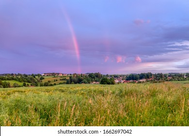 Rainbow over the summer field and road after the evening storm, sunset in countryside with beautiful sky
