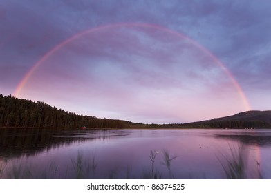Rainbow over a swedish lake with windblown reed in the foreground