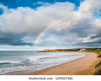 Rainbow over Torquay Back Beach, Torquay, Great Ocean Road, Victoria, Australia, with Torquay Surf Club in the distance.