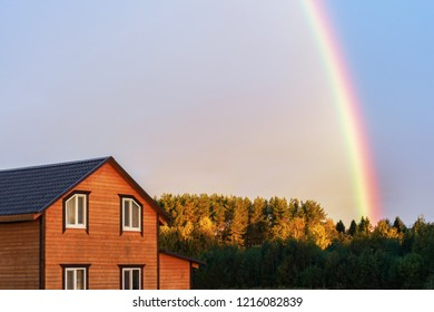 Rainbow over the wooden house with light clouds at sunrise