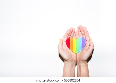 Rainbow painted heart in open palms