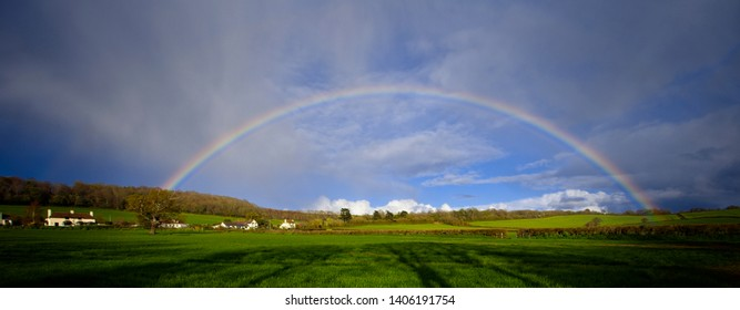 A rainbow panorama over farmland near Minehead, Somerset, England, UK.