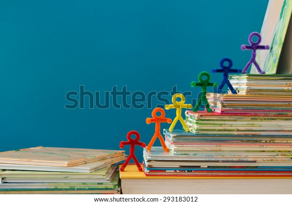 A rainbow of pipe-cleaner people walking up a stack of books as if they are climbing to success through the gaining of knowledge. A wonderful photo for multiple purposes for all nationalities.