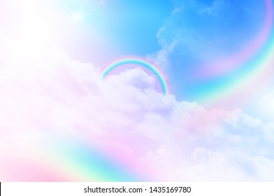 The Rainbow sky is Colorful sky with Soft clouds and a rainbow crossing. Fantasy magical sunny sky pastel background is fluffy white cloud. Freedom wallpaper concept. Sweet color dream.