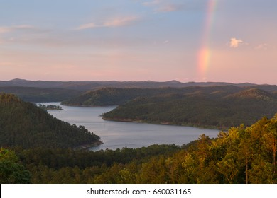 A rainbow in the sky during a beautiful sunset at Broken Bow Lake, Oklahoma.