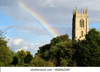 A rainbow in the sky next to a church spire among trees