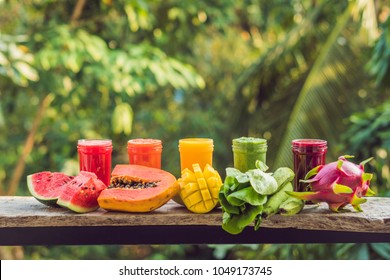 Rainbow from smoothies. Watermelon, papaya, mango, spinach and dragon fruit. Smoothies, juices, beverages, drinks variety with fresh fruits on a wooden table