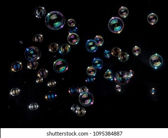 Rainbow soap bubbles on black background.