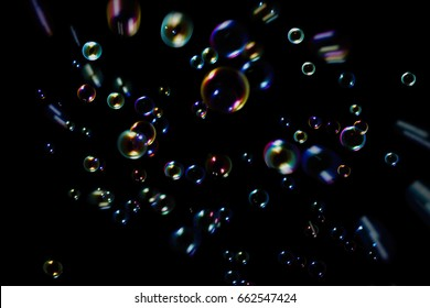 Rainbow soap bubbles on a dark background.