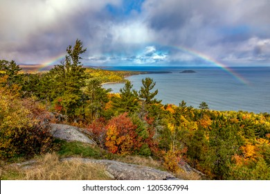 A rainbow stretches from land to Lake Superior at Sugarloaf Mountain near Marquette Michigan in Autumn