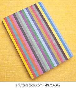 Rainbow striped notebook on a yellow background.