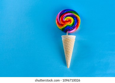 Rainbow Summer colors lollypop in ice cream wafle cone on blue background.Party, summer, happy lifestyle concept. Bright, minimalist images with copy space fotr text.