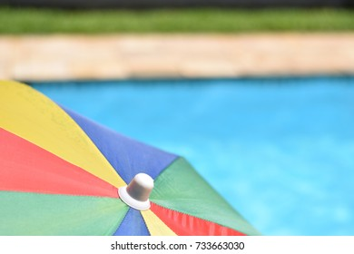 Rainbow sun umbrella  in front of a pool on a sunny summer vacation day