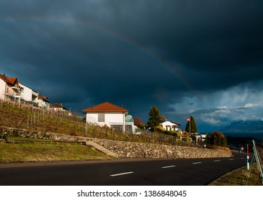 Rainbow in Switzerland. Rainbow in Mont sur Rolle. Stormy sky over village. Small houses near the road. Dark sky with the rainbow.