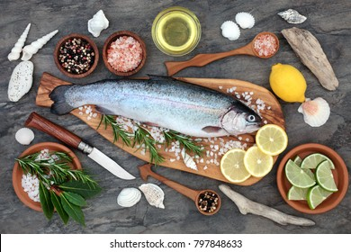 Rainbow trout health food on an olive wood board with seasoning. Very high in omega 3 fatty acid and beneficial to maintain a healthy heart.