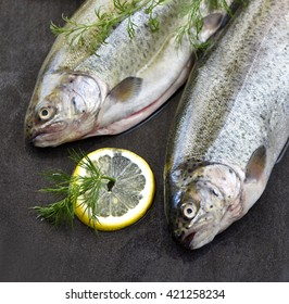 Rainbow trout on a stone board, with herbs and lemon - Shutterstock ID 421258234