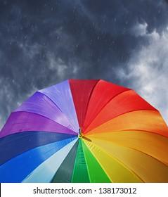 Rainbow umbrella on stormy sky background in heavy rain