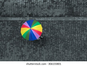 rainbow umbrella on wet pavement, shot from above