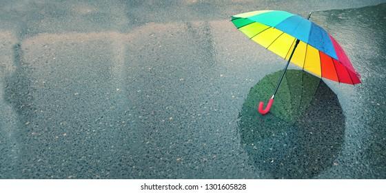 rainbow umbrella in puddle, rainy weather. autumn rainy season. colorful umbrella on street. fall time, autumn background, copy space. banner