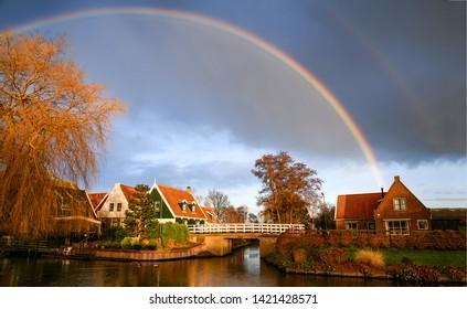 Rainbow village river houses landscape. Village river bridge rainbow sky. Rainbow after rain over village river. Rainbow river bridge landscape
