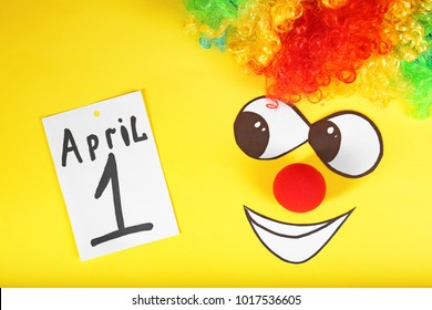 """Rainbow wig, clown nose and note with phrase """"1st April"""" on color background. Fool's day composition"""
