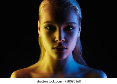Rainbow woman silhouette, woman in colorful bright lights posing in studio. Art design, colorful girl Over black background