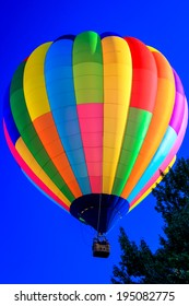 A Rainbow-colored hot air balloon soaring over treetops under a blue sky