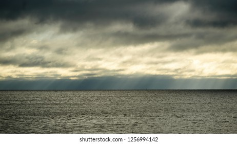 Rainclouds dispersing, letting subtle rays of sunshine through over a dark and sinister horizon.