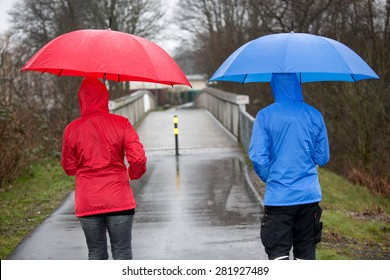 A raincoat dressed couple are walking in the rain