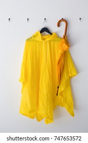 Raincoat and umbrella hanging on hook against wall