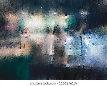 Raindrop on glass window in rainy season at cafe