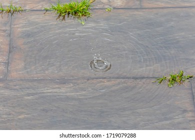 raindrop splashing into a puddle on slate floor