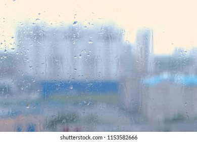 Raindrops flow down the window close-up. View of sity and road from wet window, blur