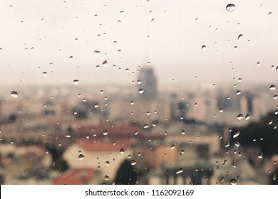 Raindrops on the dirty glass, behind the glass blurred panorama of the old colored city, abstract retro nostalgically background