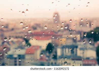 Raindrops on the dirty glass, behind the glass blurred panorama of the old colored city, abstract cozy retro nostalgically background