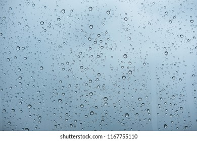 raindrops on glass window of car with cloudy sky in the background