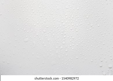 Raindrops on a grayish white background. Rainy season concept.