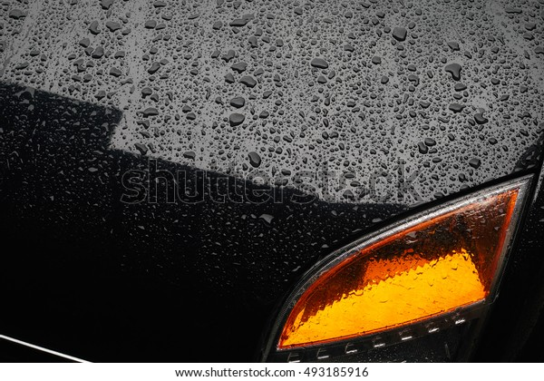 Raindrops on the hood of a black car.