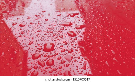 Raindrops on red car hood, after the rain.