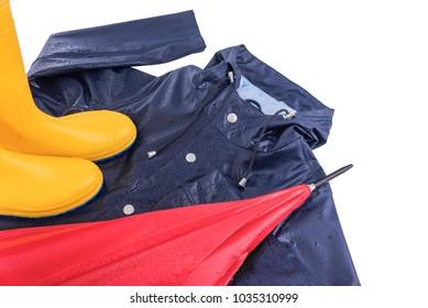 Raindrops on rubber boots, a raincoat and an umbrella. Close-up.