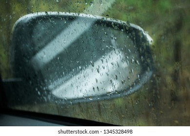 raindrops on the side window and car mirror