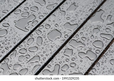 Raindrops on the surface. Water on the surface. After the rain. Water drops. Wooden boards.