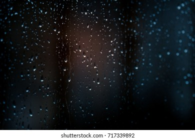 Raindrops on window with blurred background.