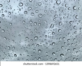 Raindrops on the window. Clouds sky on the back. The drops have beautiful black countur