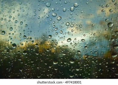 Raindrops on window with clouds and sky in the background
