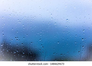 Raindrops on window glass with blur background