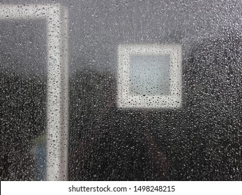 Raindrops on Window Glass with Dark Black Wooden House Facade Background and Windows