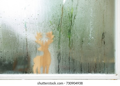 Raindrops on window glass and deer sculptured wood background.