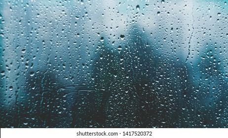 raindrops on a window. Rainy window at night. Drops on the black glass. dark blue wet, drops of water rain on glass background. concept of autumn weather.