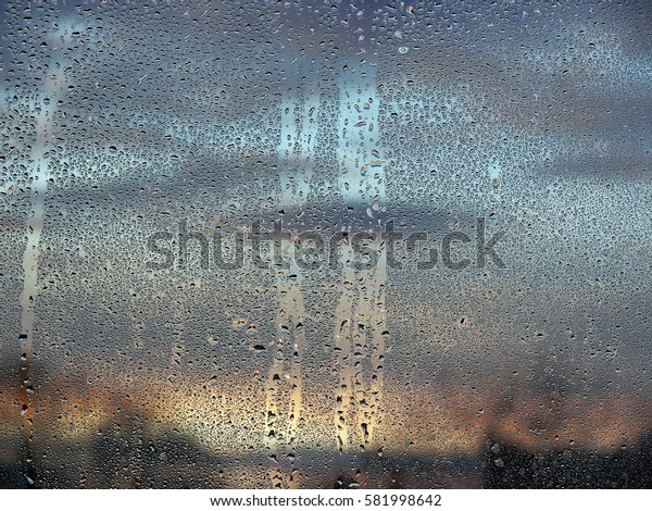 Raindrops on the windshield; in the background sky and clouds.